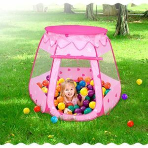 A girl playing in the pink tent with balls