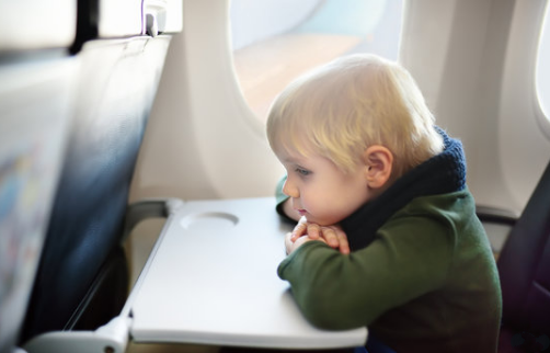 A toddler boy sitting by aircraft window during the flight