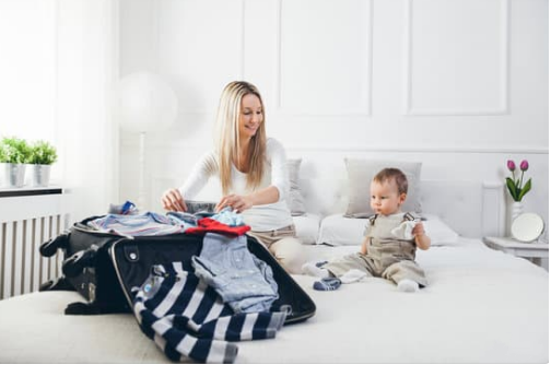 A mom packing the luggage with a toddler boy