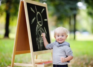 A toddler boy drawing on board