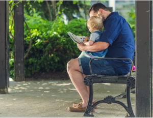 Man reading book to toddler on the bench