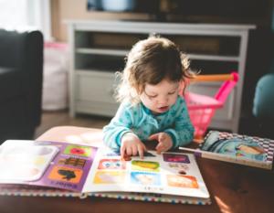 Toddler girl reading books