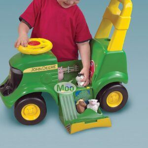 a boy playing with the John Deere Activity Tractor