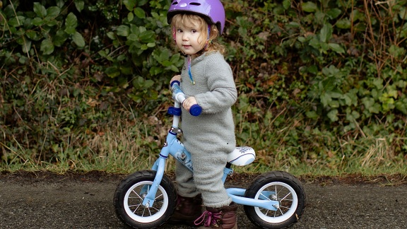 a toddler girl riding a balance bike
